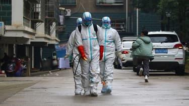 Des employés désinfectent les rues d'une résidence dans la province de Jiujiang, non loin de Wuhan, en Chine.