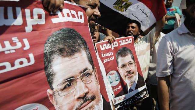 Des manifestants brandissent des portraits de Mohamed Morsi, mardi 2 juillet, au Caire.