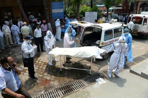 Le corps d'une victime du coronavirus est sorti d'une ambulance pour être incinéré au crématorium du site de Nigambodh Ghat, le 3 juin 2020 à New Delhi