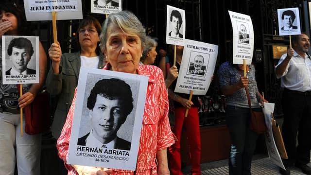 Beatriz Cantarini de Abriata, mère de Hernan Abriata, arrêté en 1976 en Argentine et depuis disparu, brandit un portrait de son fils, avec des proches, devant l'ambassade de France, à Buenos Aires.