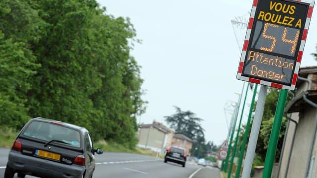 Des voitures passent le 2 juin 2011 devant un panneau indicateur de vitesse sur une route nationale près de Vienne (Rhône).