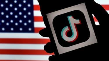 Le logo de TikTok s'affiche sur l'écran d'un téléphone portable, avec le drapeau américain en toile de fond, le 3 août 2020 à Arlington (Etats-Unis)