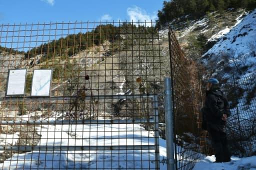 """Un homme regarde à travers les barrières """"sanctuarisant"""" le site du crash près du Vernet (Alpes-de-Haute-Provence), le 18 mars 2016"""