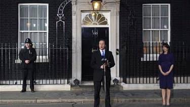 Le nouveau Premier ministre David Cameron prend la parole avant de faire son entrée au 10, Downing Street. Son gouvernement de coalition réservera cinq places aux libéraux-démocrates, dont le poste de vice-Premier ministre à son chef, Nick Clegg. /Photo p
