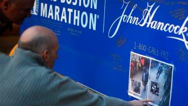 A Boston deux hommes regardent les photos de deux suspects dans l'enquête sur le double attentat à la bombe de Boston diffusées par le FBI jeudi. /Photo prise le 18 avril 2013/REUTERS/Brian Snyder