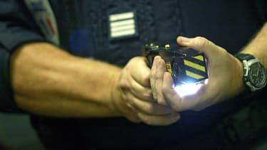 Un policier teste le 15 septembre 2004 à l'hôtel de police de Lyon un pistolet paralysant. Photo d'illustration.