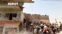 Secouristes et habitants sur les lieux d'une explosion dans le centre de Bagdad. Des explosions coordonnées ont détruit sept bâtiments dans plusieurs quartiers de la capitale irakienne, faisant 35 morts et 140 blessés. /Photo prise le 6 avril 2010/REUTERS