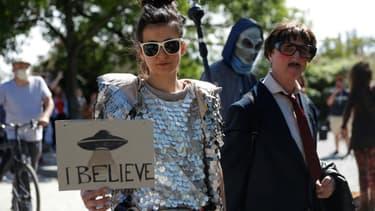 """Une femme tient une pancarte """"je crois"""" aux ovnis, lors d'une manifestation contre les tenants des théories du complot à Berlin le 30 mai 2020"""