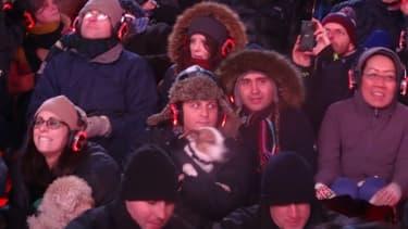 Des spectateurs tiennent leur chien lors d'un concert pour chiens à Times Square à New York le 4 janvier 2016