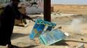 Un insurgé libyen tire sur un portrait de Mouammar Kadhafi, à Ajdabiah, dans l'est du pays. La France reste hostile à un déploiement de forces sur le terrain en Libye pour guider les frappes aériennes, malgré les appels en ce sens lancés par certaines per