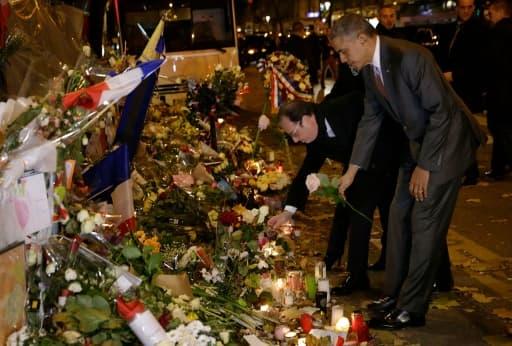 Les présidents français François Hollande et américain Barack Obama, se recueillent une rose blanche à la main, devant le Bataclan le 30 novembre 2015 à Paris