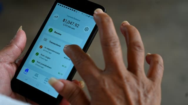 Une femme utilise l'application Bitcoin dans un magasin de El Zonte (Salvador) le 4 septembre 2021