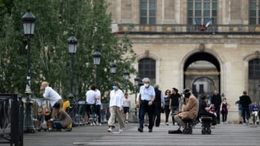 Des personnes masquées en train de marche sur le pont des Arts à Paris, le 9 mai 2020.