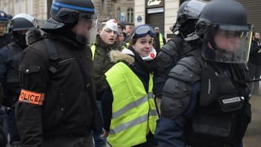 Une manifestante arborant un gilet jaune, interpellée samedi matin, sur les Champs Elysées.