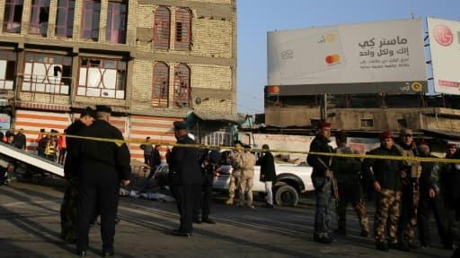 Des membres des forces de sécurité irakiennes installent un périmètre de sécurité après un double attentat suicide dans le centre de Bagdad, le 15 janvier 2018