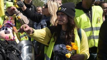 Une manifestante tend des fleurs à des CRS à Paris.