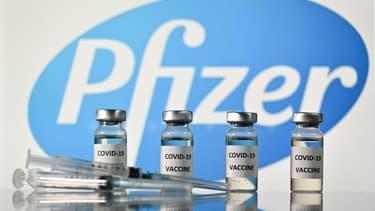 Photo d'illustration prise le 17 novembre 2020 montrant des flacons et des seringues, avec le logo du laboratoire américain Pfizer