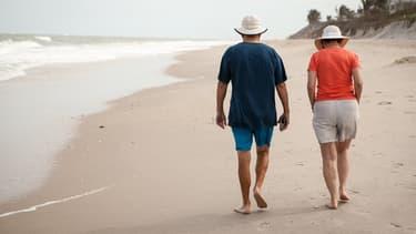 Deux personnes âgées se promenant sur une plage.
