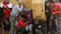 Des manifestants trouvant refuge auprès d'un blindé lors d'affrontements entre pro- et anti- Moubarak sur la place Tahrir, au Caire mercredi.