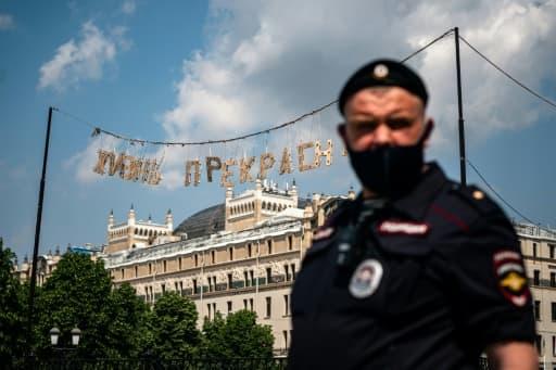 """Un policier russe masqué pose sous une banderolle qui proclame """"la vie est belle"""", dans le centre de Moscou, le 9 juin 2020."""