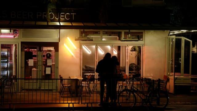 Un couple devant un bar fermé le 5 octobre 2020 (photographie d'illustrattion)