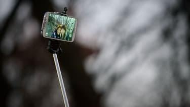 """Deux personnes prennent un selfie avec un """"selfiestick"""" (illustration)"""