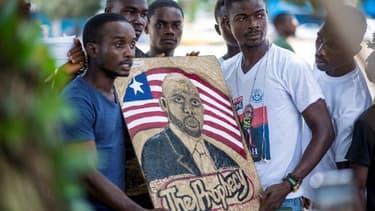 Des militants tiennent une peinture représentant le candidat à l'élection présidentielle George Weah.