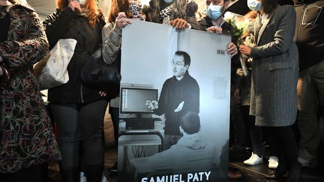 Des participants à la marche blanche en hommage à Samuel Paty portant une photo du professeur.