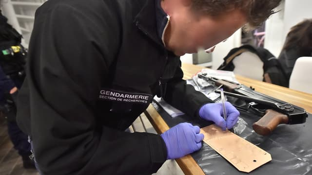 Un enquêteur examine une arme à feu. (Illustration)