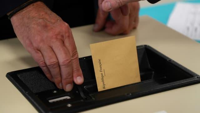 Un électeur glisse son bulletin de vote dans l'urne.