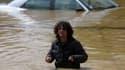 Un homme tente de traverser une rue inondée à Obrenovac, à l'ouest de Belgrade en Serbie.