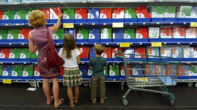 Une mère et ses deux enfants font leus courses dans une grande surface.