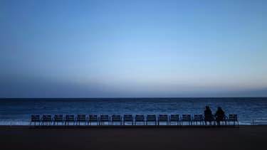 Deux personnes goûtent l'air du soir sur la Promenade des Anglais, à Nice le 21 février 2021