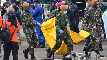 Des soldats indonésiens transportent des objets récupérés sur le vol SJ182 de Sriwijaya Air au port de Tanjung Priok, au nord de Jakarta, le 12 janvier 2021.