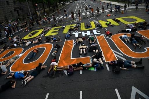 """Des manifestants allongés autour d'une inscription invitant à """"couper les vivres de la police"""", le 6 juin 2020, à Washington"""