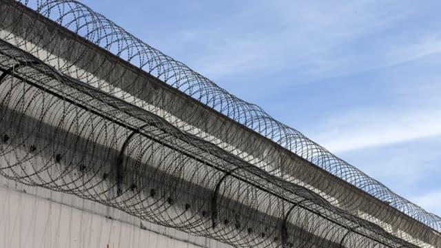 Un mur surmonté de barbelés qui entoure une prison (image d'illustration) -