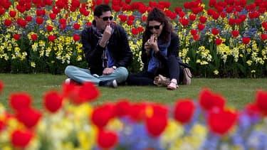 Un couple partage un moment intime dans un parc.