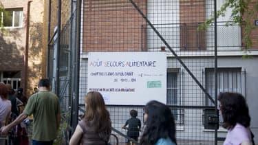 Bénéficiaire de l'aide alimentaire, faisant la queue devant un local de l'association Août secours alimentaire, à Paris.