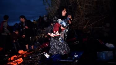 Une femme porte son enfant après une traversée éprouvante entre la Turquie et la Grèce, le 24 octobre 2015 - Photo d'illustration