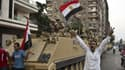 Des Egyptiens saluent mercredi l'action de l'armée dans une rue du Caire.