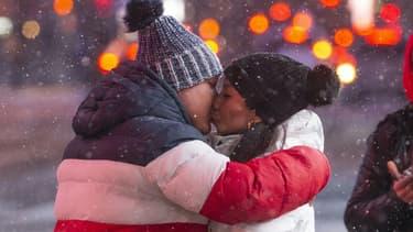 Un couple s'embrasse sous la neige sur Times Square, à New York, le 31 janvier 2021 (Photo d'illustration)