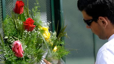 Un homme se recueille devant un bouquet de fleurs, en hommage aux victimes du train.