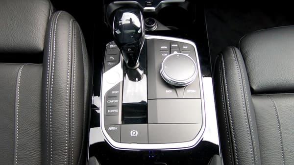 La console épurée avec le bouton de démarrage, les modes de conduite, le levier de vitesse et la molette d'accès aux fonctions de confort et réglages.