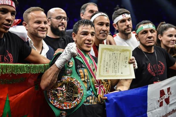 Nordine Oubaali (au centre) avec son équipe et sa ceinture de champion du monde WBC des coqs