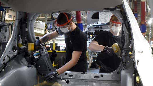 """Des ouvriers en train d'assembler la voiture """"électrifiée"""" la plus produite en France."""