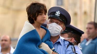 Un enfant secouru par un policier maltais, samedi.