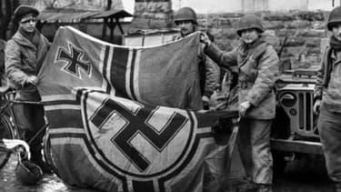 Des soldats anglais tenant un drapeau nazi au moment de la libération (photo d'illustration)