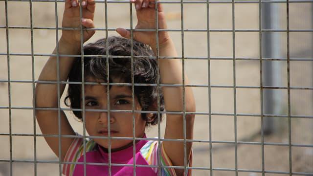 Une petite fille, les mains accrochées à la clôture regarde en direction des officiers du camp.