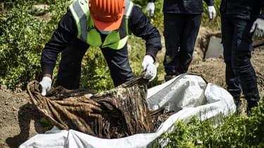 Un homme sur une fosse commune à Raqa en avril 2019