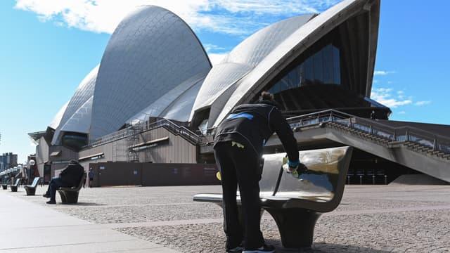 Un employé municipal nettoie les sièges publics à l'extérieur de l'Opéra de Sydney, le 26 juin 2021, après l'annonce des autorités d'un confinement de deux semaines.